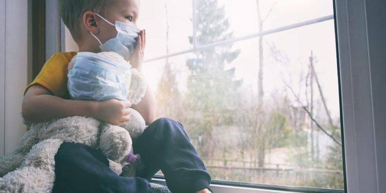 Kind mit Schutzmaske am Fenster